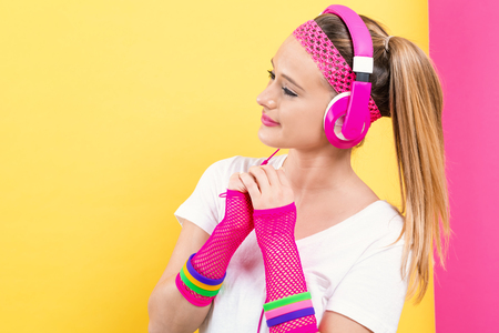 Woman in 1980s fashion with headphones on a split yellow and pink background