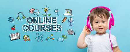 Online courses with toddler boy with headphones on a blue background Stock Photo