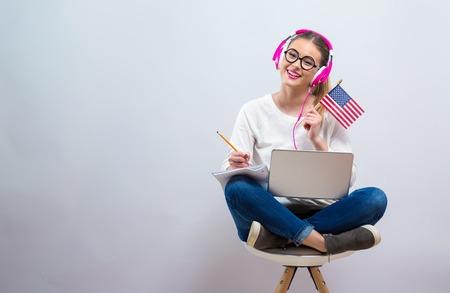 Jonge vrouw met de vlag van de V.S. met behulp van een laptopcomputer op een grijze achtergrond