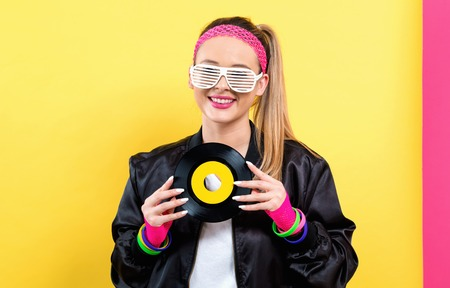 Woman in 1980s fashion holding a record on a split yellow and pink background Stockfoto
