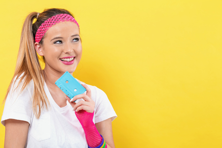 Woman in 1980s fashion holding a cassette tape on a yellow background