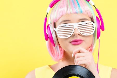 Woman in a colorful wig holding a vinyl record on a purple background