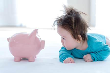 Baby boy with a piggy bank in childcare costs or savings theme 스톡 콘텐츠 - 111826649