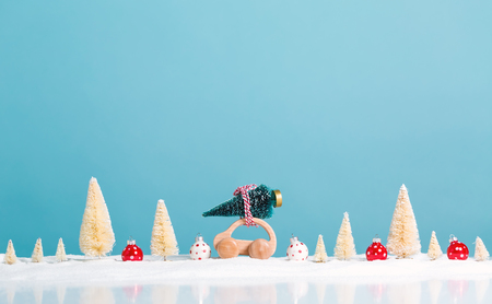 Miniature wooden car carrying a Christmas tree on a blue background Archivio Fotografico