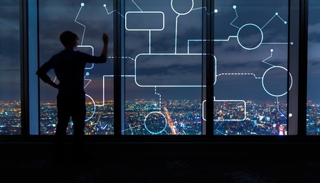 Flowchart with man writing on large windows high above a sprawling city at night
