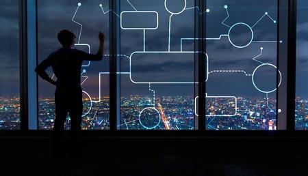 Stroomdiagram met man die 's nachts op grote ramen hoog boven een uitgestrekte stad schrijft Stockfoto