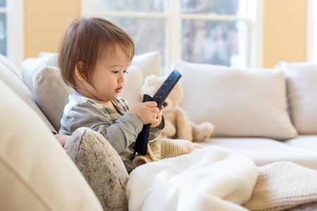 Little toddler boy with a TV remote control
