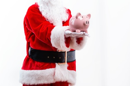 Santa holding a piggy bank isolated on white background
