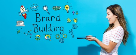 Brand building with young woman using her tablet Imagens