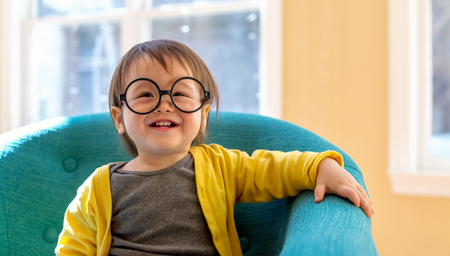 Happy toddler boy with glasses playing in a big chair