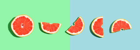 Halved fresh grapefruits on bright color background Stock fotó