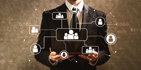 Social connections with businessman holding a tablet computer on a dark vintage background