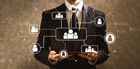Conexiones sociales con el empresario sosteniendo una tableta sobre un fondo oscuro de la vendimia Foto de archivo