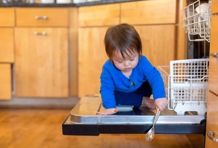 Toddler boy playing around in the kitchen