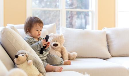 Petit garçon en bas âge avec une télécommande de télévision