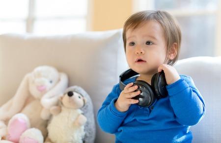 Toddler boy listening to music with big headphones 写真素材