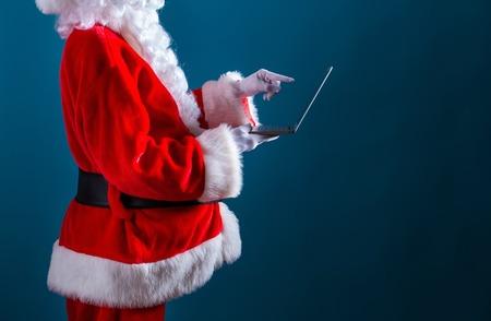 Santa using a laptop on a dark blue background