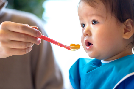 Toddler boy eating food in the kitchen
