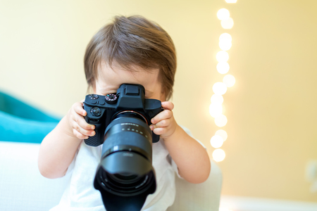 Toddler boy with a professional DSLR camera