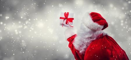 Santa holding a Christmas gift on a shiny light background