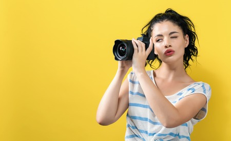 Young woman with a professional digital SLR camera on a yellow background 写真素材