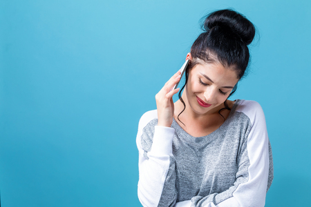 Young woman talking her the cellphone on a blue background