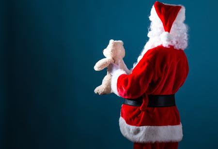Santa holding a teddy bear on a dark blue background