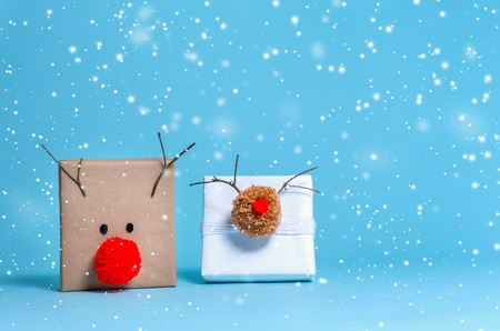 Pompom reindeer gift boxes on a blue background Stock Photo