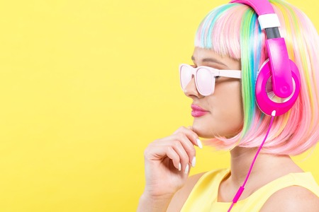 Woman in a colorful wig with headphones listening to music on a yellow background 写真素材