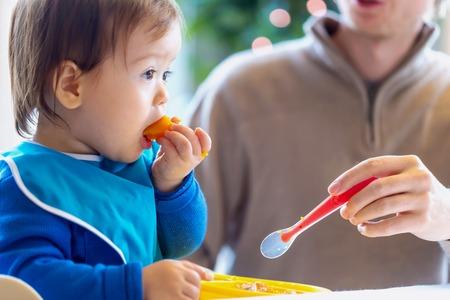 Ragazzo del bambino che mangia cibo in cucina