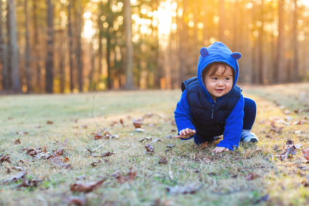 Toddler boy playing outside on an autumn day