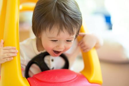 Happy toddler boy having fun playing in his toy car