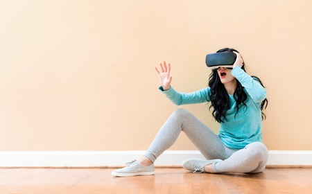 Young woman using a virtual reality headset against a big interior wall