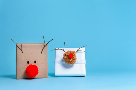 Pompom reindeer gift boxes on a blue background 免版税图像