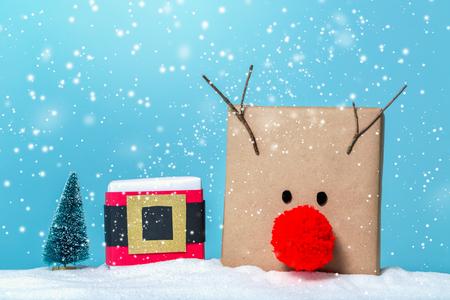 Pompom reindeer and santa belt gift boxes in a snow covered landscape