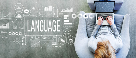 Language with man using a laptop in a modern gray chair Stock Photo