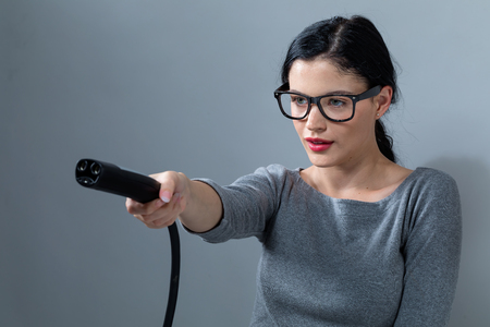 Young woman with an electric vehicle charger on a gray background Stock Photo - 112242681
