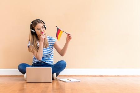 Jeune femme avec le drapeau de l'Allemagne à l'aide d'un ordinateur portable contre un grand mur intérieur Banque d'images
