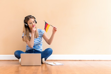 Young woman with Germany flag using a laptop computer against a big interior wall