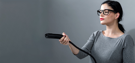 Young woman with an electric vehicle charger on a gray background Stock Photo