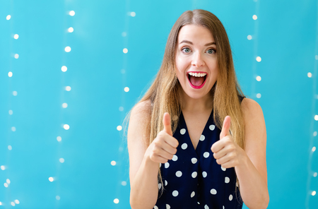 Young woman giving thumbs up on a shiny light background 版權商用圖片