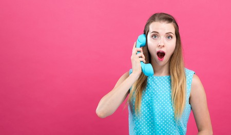 Young woman talking on an old fashioned retro phone on a pink background Stock Photo