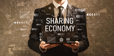 Sharing economy with businessman holding a tablet computer on a dark vintage background Banque d'images - 112586181