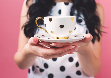 Young woman holding a cup of coffee on a solid background 스톡 콘텐츠