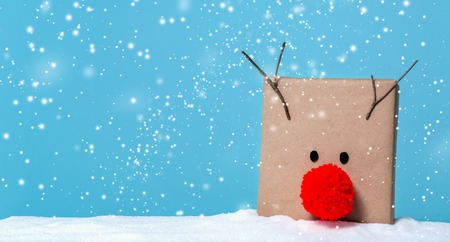 Pompom reindeer gift box in a snow covered landscape