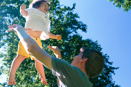 Happy toddler boy being thrown in the air outside Stock Photo