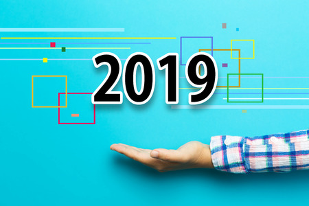 2019 new year concept with hand on blue background Stock Photo