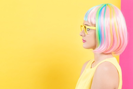 Young woman in a colorful wig with sunglasses on a split yellow and pink background Stock Photo