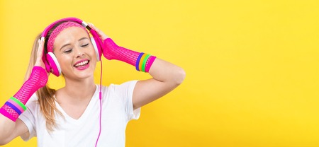 Woman in 1980s fashion with headphones on a yellow background Stockfoto - 113092464