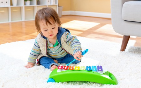 Toddler boy playing with a musical instrument